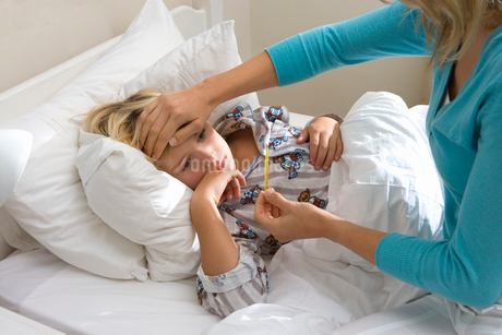Mother taking daughter's (8-10) temperature, close-upの写真素材 [FYI02111474]