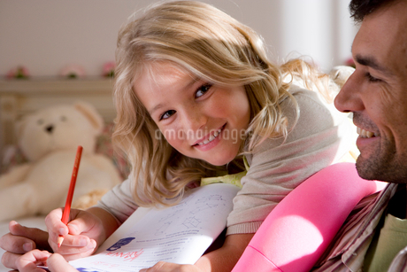 Girl (6-8) doing homework by father, smiling, portraitの写真素材 [FYI02111492]