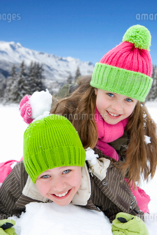 Brother and sister (6-8) wearing woolen hats, lying in snow, smiling, portrait, close-upの写真素材 [FYI02111551]