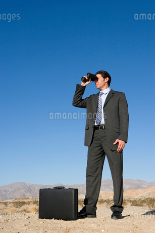 Businessman with briefcase using binoculars in desert, low angle viewの写真素材 [FYI02111565]