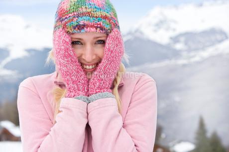 Young woman wearing woolen hat in snow, smiling, portrait, mountain range in backgroundの写真素材 [FYI02111627]