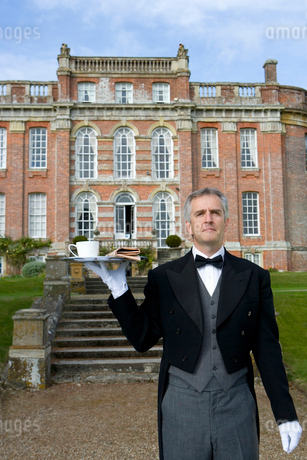 Mature butler with tray of tea by manor house, low angle viewの写真素材 [FYI02111662]