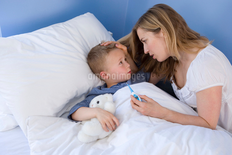 Boy (4-6) in bed, mother taking temperature, elevated viewの写真素材 [FYI02111665]