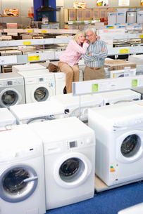 Mature couple shopping for appliances, woman embracing man with arms crossedの写真素材 [FYI02111707]