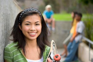Teenage girl (13-15) with skateboard by friends outdoors, smiling, portraitの写真素材 [FYI02111732]