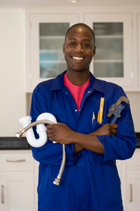 Plumber with wrench and pipes in kitchen, smiling, portraitの写真素材 [FYI02111768]