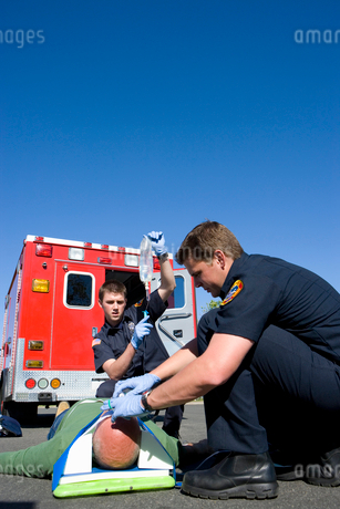 Paramedic and colleague helping man on stretcher by ambulance, low angle viewの写真素材 [FYI02111815]