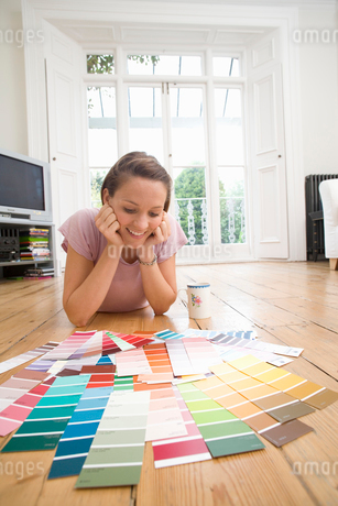 Young woman lying on stomach on floor looking at paint swatches, smilingの写真素材 [FYI02111829]