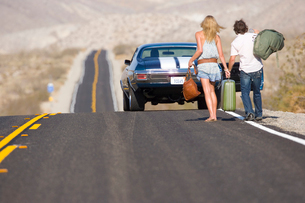 Young couple hitchhiking on desert road, walking towards car, rear viewの写真素材 [FYI02111842]