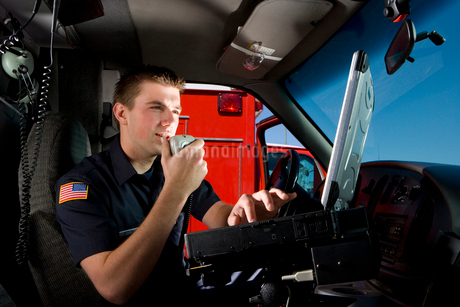 Paramedic in cab of ambulance, using communication equipment, low angle viewの写真素材 [FYI02111879]