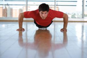 Man doing push-ups in gym studio, portraitの写真素材 [FYI02111893]