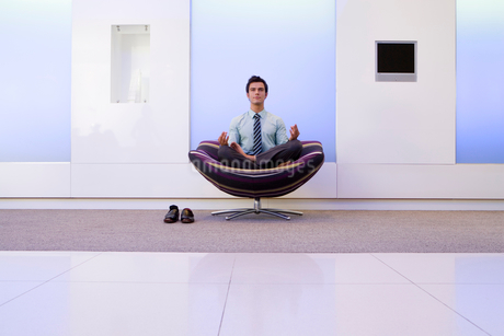 Businessman meditating in armchair in foyer, portraitの写真素材 [FYI02111952]