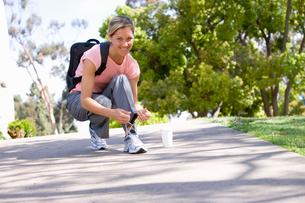 Woman doing up shoelace, smiling, portraitの写真素材 [FYI02111962]