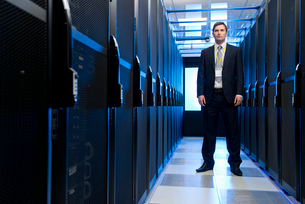 Manager standing in aisle of storage cabinets in data centerの写真素材 [FYI02111982]