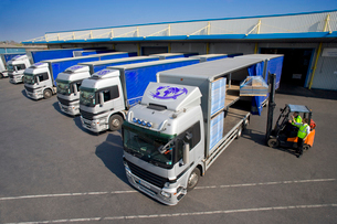 Worker driving forklift loading semi-truck on loading dockの写真素材 [FYI02112038]