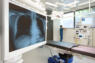 Surgeon standing in hospital operating room with x-ray and equipmentの写真素材 [FYI02112057]