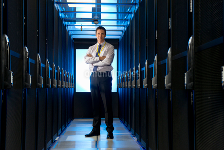Manager standing in aisle of storage cabinets in data centerの写真素材 [FYI02112088]