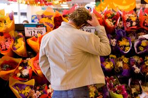 Man choosing bouquet of fresh flowers in grocery storeの写真素材 [FYI02112101]