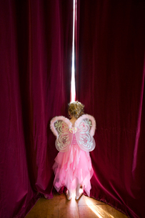 Ballerina girl (4-6) with fairy wings peeking out gap in stage curtains, rear viewの写真素材 [FYI02112126]