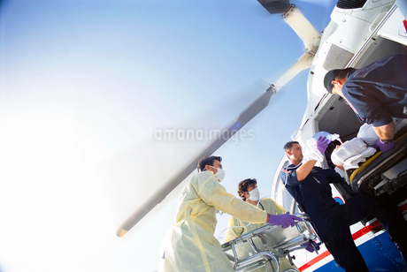 Doctors and paramedics transferring patient from emergency airlift helicopterの写真素材 [FYI02112139]