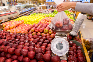 Woman weighing apples in grocery storeの写真素材 [FYI02112153]