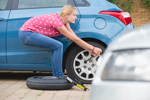 Woman Changing Flat Tyre On Carの写真素材 [FYI02112208]