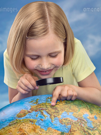 Young girl looking through a magnifying glass at a globe, studio shotの写真素材 [FYI02112250]