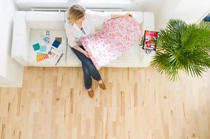 Woman on sofa looking at wallpaper sampleの写真素材 [FYI02112254]