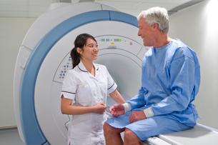 Radiologist helping patient with MRI scanning machineの写真素材 [FYI02112264]