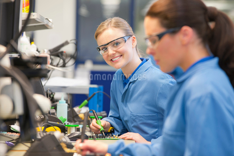 Portrait of smiling technician soldering circuit board on production line in manufacturing plantの写真素材 [FYI02112278]