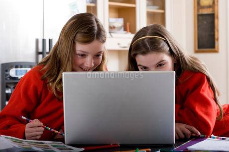 Sisters using laptop to do homeworkの写真素材 [FYI02112298]