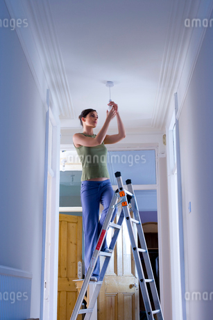 Woman on ladder changing light bulb, low angle viewの写真素材 [FYI02112343]