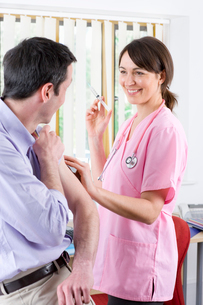 Smiling nurse holding syringe and preparing to give man an injectionの写真素材 [FYI02112369]
