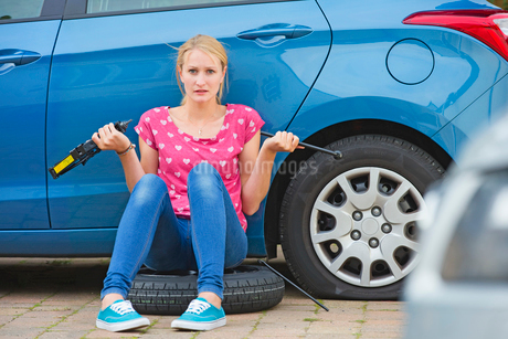 Frustrated Woman Trying To Change Flat Tyre On Carの写真素材 [FYI02112436]
