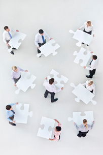 Business people holding large jigsaw piecesの写真素材 [FYI02112441]