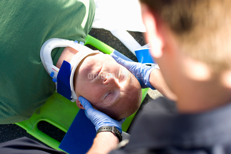 Paramedic helping man on stretcher with head in brace, elevated viewの写真素材 [FYI02112466]