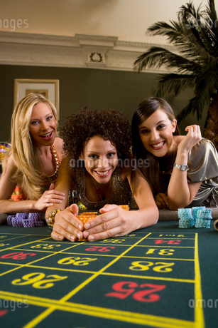 Young woman collecting pile of gambling chips from roulette table, flanked by friends, smiling, portの写真素材 [FYI02112496]