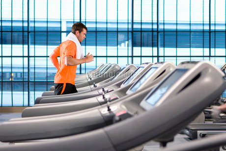 Man running on treadmill with towel around neck in health clubの写真素材 [FYI02112513]
