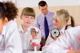 School girls working with biology model in classroomの写真素材 [FYI02112539]