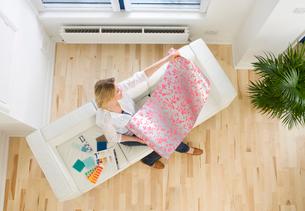 Woman on sofa looking at wallpaper sampleの写真素材 [FYI02112602]