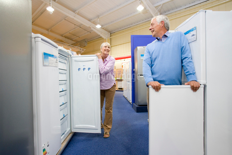 Mature couple shopping for appliances, smiling at each other, low angle viewの写真素材 [FYI02112611]