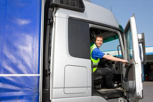 Truck driver sitting in cab of semi-truck and closing doorの写真素材 [FYI02112624]