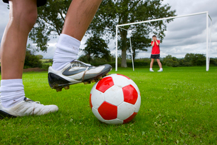 Close up of soccer player aiming ball at frightened goalieの写真素材 [FYI02112674]