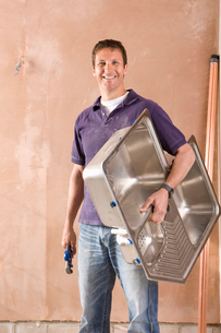 Smiling male plumber holding wrench and sink ready to be installedの写真素材 [FYI02112690]
