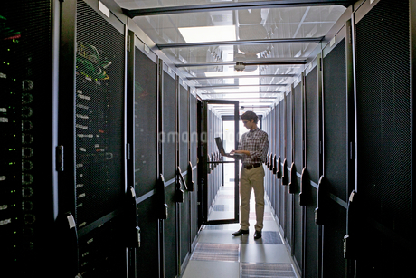 Technician with laptop, checking aisle of server storage cabinets in data centerの写真素材 [FYI02112691]