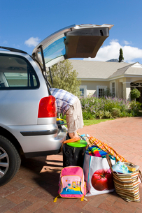 Man loading boot of car with luggage, side viewの写真素材 [FYI02112703]