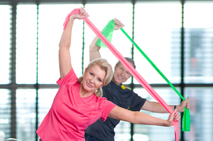 Portrait of couple stretching with resistance bands overheadの写真素材 [FYI02112746]