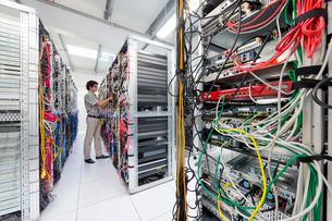 Technician checking cables in Server room of data centerの写真素材 [FYI02112757]