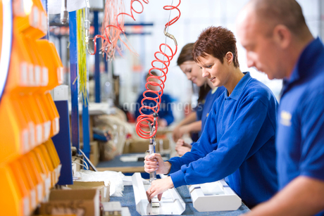 People working on aluminium light fittings on production line in factoryの写真素材 [FYI02112758]