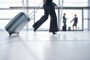 Rushing businesswoman pulling suitcase in airportの写真素材 [FYI02112759]